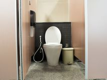 Toilet door opening and white flush toilet with a trash cans and box of toilet paper. Toilet door opening and white flush toilet with a trash cans and box of stock photography