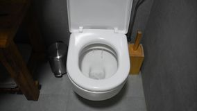 Toilet Flushed. Closeup view of water flushing down into the toilet bowl in bathroom. Water flows into the toilet. stock video footage