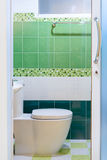 Toilet with green tile view Stock Images