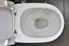 Toilet in the house with yellow stains from the water, cleaning unit with detergent on the rim stock image