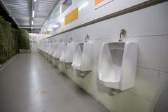 Toilet men`s room.Close up row of outdoor urinals men public toilet,Closeup white urinals in men`s bathroom stock photography