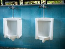 Toilet men`s room.Close up row of outdoor urinals men public toi Royalty Free Stock Image