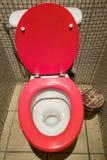 Toilet met rode zitting in het betegelde toilet stock foto's