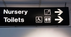 Toilet nursery sign and arrow in airport Stock Photo