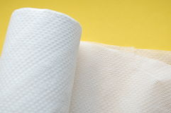 Toilet paper. A  role of toilet paper with a yellow background Stock Image
