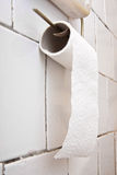 Toilet paper. A roll of toilet paper hanging on tiled wall Stock Image