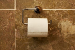 Toilet paper. Hanging on a marble wall Royalty Free Stock Photo