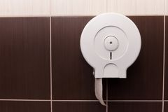 Toilet paper dispenser. Hanging on the wall close-up royalty free stock image