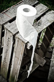 Toilet Paper Roll. On an old wooden crate royalty free stock images