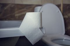Toilet paper roll on the edge of the bath. On the background of toilet.  Royalty Free Stock Images