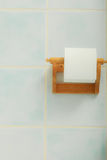 Toilet paper roll hanging in bathroom on wall Stock Photos