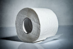 Toilet paper roll. Toned blue laying on table Royalty Free Stock Photography