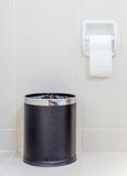 Toilet paper and  trashcan in white hygeine restroom. Royalty Free Stock Photos