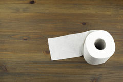 Toilet paper on a wooden background Royalty Free Stock Photos