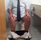 Toilet Problem. A caucasian adult man wearing white shirt and tie on toilet seat with his trousers and boxers around his ankles Stock Photos