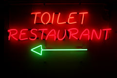 Toilet-restaurant. Closeup of a badly worded neonsign in a restaurant Stock Photos