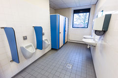 Toilet room for men with urinals sinks and towel dispenser Royalty Free Stock Photos