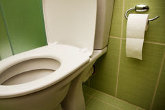 Toilet seat and paper in bathroom Stock Photos