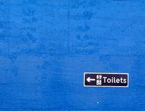 Toilet sign on a blue wall Stock Images