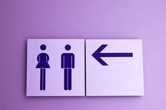 Toilet sign and direction. On purple background Royalty Free Stock Photography