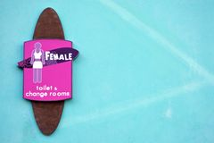Females Toilet Sign for females. Toilet sign for females in the shape of a surf board at the entrance to a public toilet royalty free stock photos