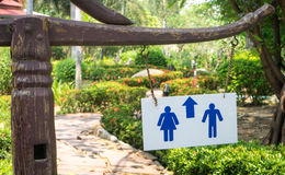 Toilet sign in Garden on wooden pole. Direction to Bathroom in garden. Restroom signage Stock Photo