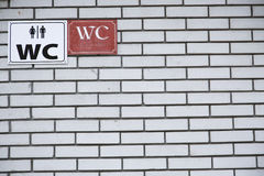Toilet sign for man and female on white brick wall Stock Photo