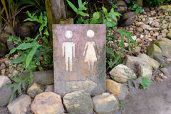 Toilet sign. Man and a lady toilet sign Made from plaster surrounded by trees Royalty Free Stock Photography
