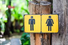 Toilet Sign man and woman draw on yellow sign wood for backgro Stock Images