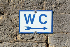 Toilet sign on old stone wall Stock Images