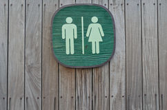 Toilet sign on vertical stripe wood panel. Green artificial wood toilet sign on vertical stripe wood panel with nail head in horizontal order Royalty Free Stock Photos
