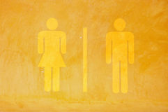 Toilet sign on yellow grunge cement wall. Toilet symbol Royalty Free Stock Image