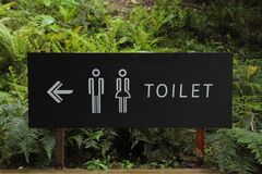 Toilet Signage Beside Green Leaf Stock Photo