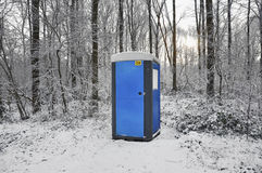 Toilet the snow. Blue mobile toilet cabin in a snow covered forest Royalty Free Stock Photos