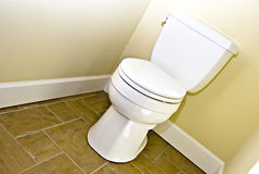 Toilet and Tile Floor. Toilet against a yellow wall on a tile floor royalty free stock photography