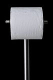 Toilet Tissue Stand. This is a photo of a metal toilet paper holder that contains a full roll on a black background Royalty Free Stock Photos