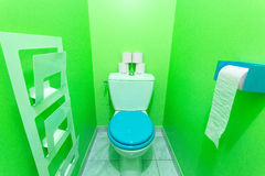 Toilet. View a clean toilets with green walls and blue toilet seat and pink paper Stock Image
