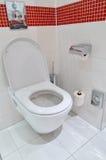 Toilet on the white floor tiles Stock Photos