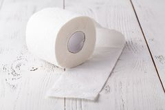 Toiletpapierbroodje op de witte houten lijst stock foto's