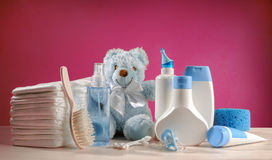 Toiletries baby with diapers and pacifiers. And pink background Stock Images