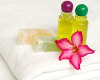 Toiletries and flower on white towel. Body soap, shampoo, therapy stone and flower Royalty Free Stock Photos