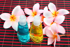 Toiletries with plumeria flower. On red mat Stock Photo