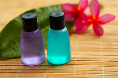 Toiletries and plumeria flower. On bamboo mat for tropical spa concept Stock Photos