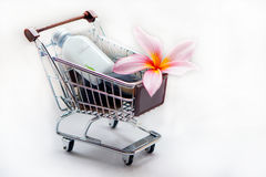 Toiletries with plumeria flower and trolley. For tropical spa concept, isolated on white background Stock Photo