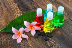Toiletries with stones and plumeria flower. On wooden floor Stock Photography
