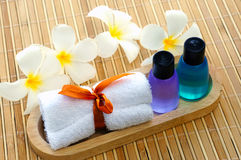 Toiletries with towel and plumeria flower. On wooden floor Royalty Free Stock Photos