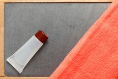 Toiletry tube and towel scene. The toiletry tube put on slate board floor surface represent the toiletry material and travel industry concept related idea Stock Photos