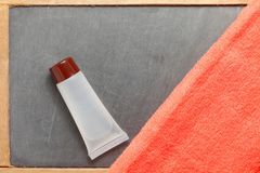Toiletry tube and towel scene. The toiletry tube put on slate board floor surface represent the toiletry material and travel industry concept related idea Stock Image