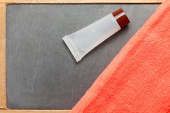 Toiletry tube and towel scene. The toiletry tube put on slate board floor surface represent the toiletry material and travel industry concept related idea Stock Photo