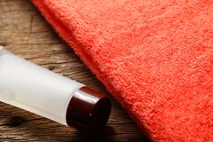 Toiletry tube and towel scene. The towel and toiletry tube on wooden floor surface represent the toiletry material and travel industry concept related idea Stock Photography